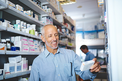 Buy stock photo Cropped shot of a handsome mature man looking for medication in a pharmacy