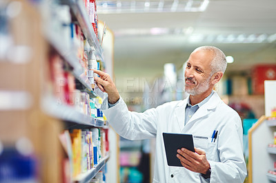 Buy stock photo Cropped shot of a handsome mature male pharmacist using a tablet while working in the pharmacy