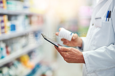 Buy stock photo Cropped shot of an unrecognizable male pharmacist using a tablet while working in the pharmacy