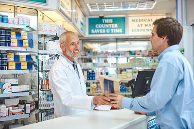 Buy stock photo Cropped shot of a handsome mature male pharmacist helping a customer in the pharmacy