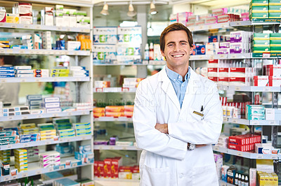 Buy stock photo Cropped portrait of a handsome young male pharmacist standing with his arms crossed in the pharmacy