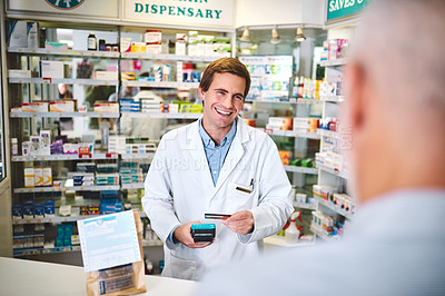 Buy stock photo Cropped shot of a handsome young male pharmacist helping a customer in the pharmacy