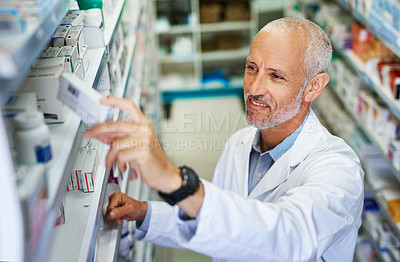 Buy stock photo Shot of a mature pharmacist doing inventory in a pharmacy