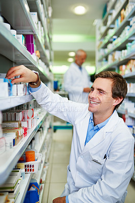 Buy stock photo Shot of a young pharmacist doing inventory in a pharmacy