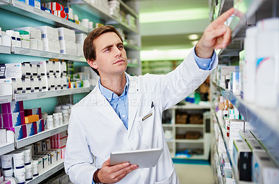 Buy stock photo Shot of a young pharmacist using a digital tablet in a pharmacy