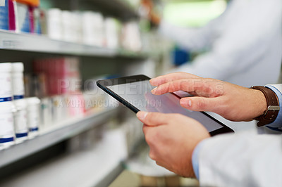 Buy stock photo Cropped shot of a pharmacist using a digital tablet in a pharmacy