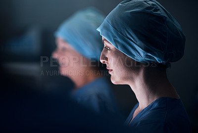 Buy stock photo Shot of a medical practitioner in an operating theatre with her colleague in the background