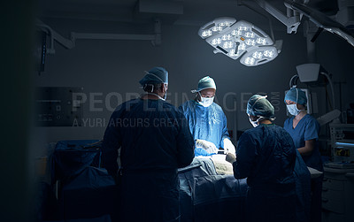 Buy stock photo Shot of a team of surgeons performing a surgery in an operating theatre
