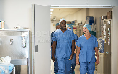 Buy stock photo Shot of a team of surgeons walking in a hospital