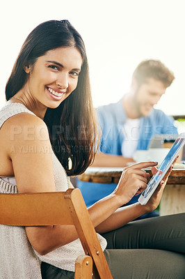 Buy stock photo Portrait of a young businesswoman using a digital tablet while having a meeting with her colleagues outdoors