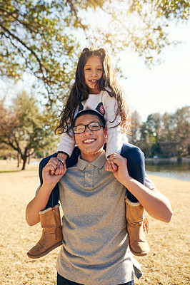 Buy stock photo Cropped shot of a teenage boy carrying his adorable little sister on his shoulders