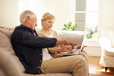 Buy stock photo Shot of a senior couple using a laptop together on the sofa at home