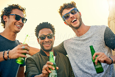 Buy stock photo Shot of a group of young friends hanging out and having drinks together outdoors