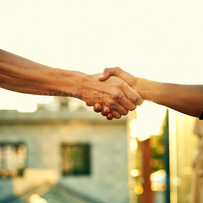 Buy stock photo Cropped shot of two men shaking hands outdoors