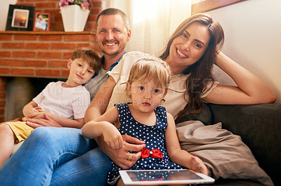 Buy stock photo Portrait of a happy young family of four relaxing together on the sofa at home