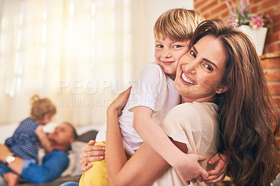 Buy stock photo Portrait of a happy little boy hugging his mother during family playtime at home