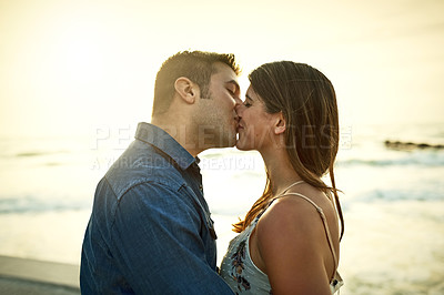 Buy stock photo Cropped shot of an affectionate young couple kissing while standing on the beach