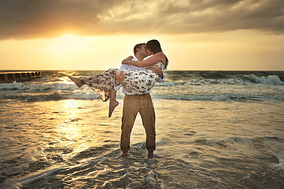 Buy stock photo Full length shot of a handsome young man kissing his girlfriend while carrying her on the beach