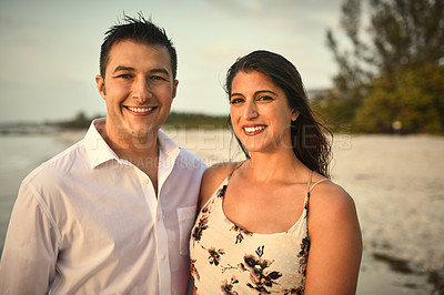Buy stock photo Cropped portrait of an affectionate young couple standing side by side on the beach