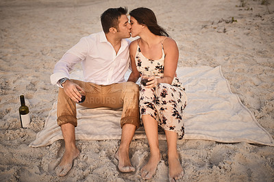 Buy stock photo High angle shot of an affectionate young couple kissing while sitting on the beach