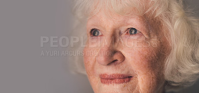 Buy stock photo Shot of a senior woman looking thoughtful against a gray background