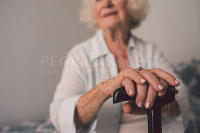 Buy stock photo Cropped shot of a senior woman with a cane in her bedroom at a retirement home