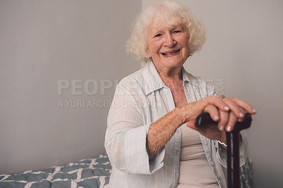 Buy stock photo Shot of a happy senior woman and a cane in her bedroom at a retirement home