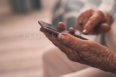 Buy stock photo Cropped shot of a senior woman using a mobile phone in a retirement home