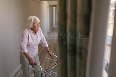 Buy stock photo Shot of a senior woman using a walker and looking thoughtfully out of a window in a retirement home