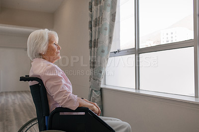 Buy stock photo Shot of a senior woman in a wheelchair looking thoughtfully out of a window in a retirement home