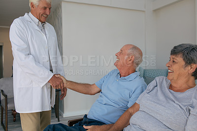Buy stock photo Shot of a senior man and woman greeting a doctor at an old age home