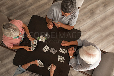 Buy stock photo High angle shot of a group of senior women playing cards together at a retirement home