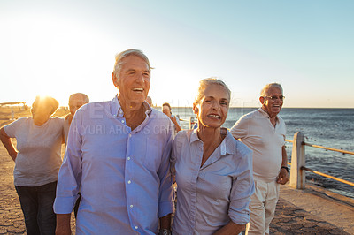 Buy stock photo Shot of a senior couple walking on the promenade with friends in the background