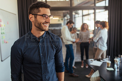 Buy stock photo Shot of a young businessman standing in an office with his colleagues in the background