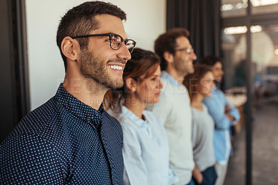 Buy stock photo Shot of a young businessman standing in an office with his colleagues in a line behind him