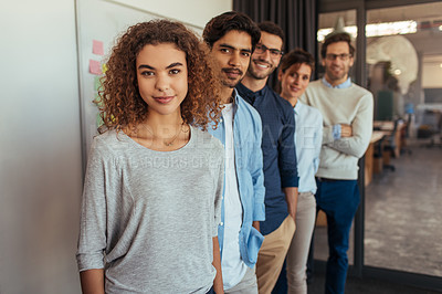 Buy stock photo Portrait of a young businesswoman standing in an office with her colleagues in a line behind her