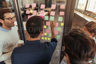 Buy stock photo High angle shot of a group of businesspeople brainstorming with notes on glass wall in an office
