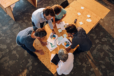 Buy stock photo High angle shot of a group of businesspeople going through paperwork in an office