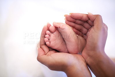 Buy stock photo Cropped shot of a mother holding her baby's feet at home
