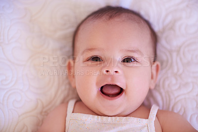 Buy stock photo High angle shot of an adorable baby girl lying down on a bed at home