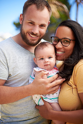 Buy stock photo Shot of a happy young man and woman bonding with their adorable baby girl outdoors