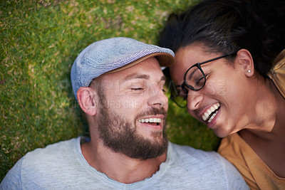 Buy stock photo High angle shot of a happy young couple lying on the grass together