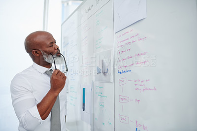 Buy stock photo Cropped shot of a handsome mature businessman looking thoughtful while looking at a whiteboard in the office