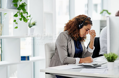 Buy stock photo Cropped shot of a young female call center agent looking stressed while working in the office alongside a male coworker