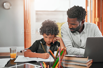 Buy stock photo Shot of a man helping his son with his homework