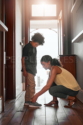Buy stock photo Shot of a woman tying her son's shoelaces