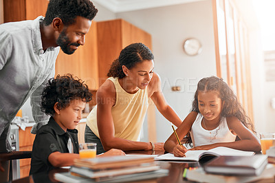 Buy stock photo Shot of parents helping their two children with their homework