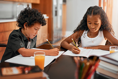 Buy stock photo Shot of a sister and brother doing their homework together