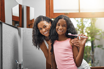 Buy stock photo Cropped portrait of an attractive young woman and her daughter brushing their teeth in the bathroom at home