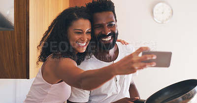 Buy stock photo Cropped shot of a young attractive couple taking a selfie in the kitchen at home